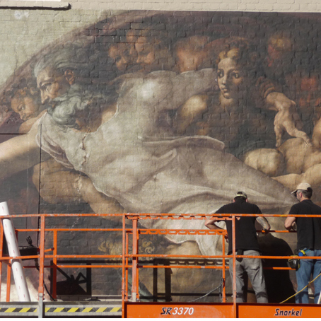"6m x 13.5m reproduction print of Michelangelo's ""Creation of Adam"" onto a brick wall"
